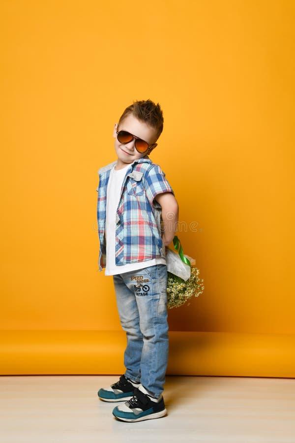 Χαριτωμένο μικρό παιδί που κρατά μια ανθοδέσμη των λουλουδιών στοκ φωτογραφίες