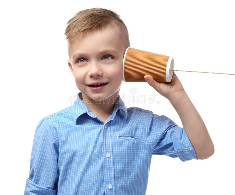 Χαριτωμένο μικρό παιδί που χρησιμοποιεί το πλαστικό φλυτζάνι ως τηλέφωνο στοκ φωτογραφίες