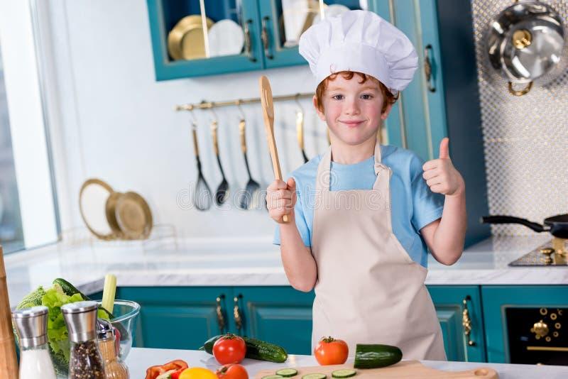 χαριτωμένο μικρό παιδί στο καπέλο αρχιμαγείρων και ποδιά που χαμογελά στη κάμερα και που παρουσιάζει αντίχειρα στοκ φωτογραφίες