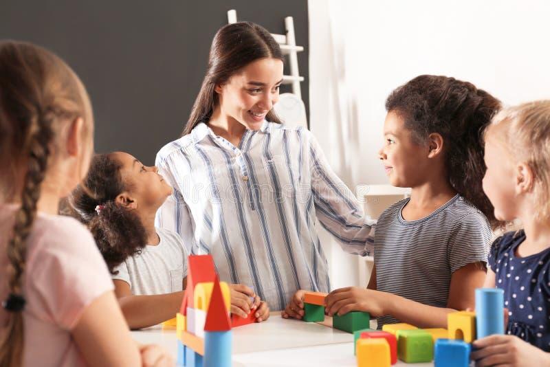 Χαριτωμένο μικρό παιχνίδι παιδιών και δασκάλων βρεφικών σταθμών με τις δομικές μονάδες στον παιδικό σταθμό στοκ φωτογραφία με δικαίωμα ελεύθερης χρήσης