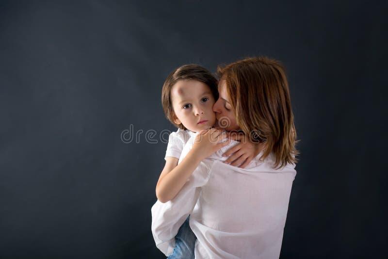 Χαριτωμένο μικρό παιδί με τη μεγάλη πρόσκρουση στο μέτωπό του από την πτώση, hugg στοκ φωτογραφίες