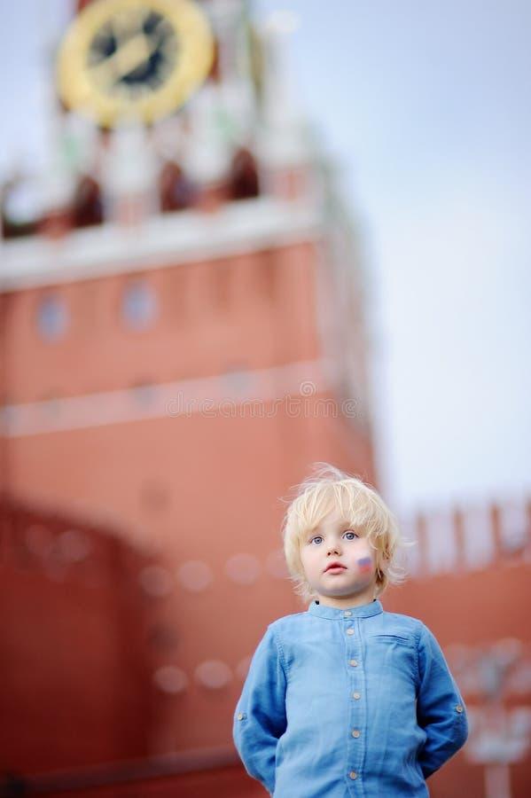 Χαριτωμένο μικρό παιδί με τη χρωματισμένη ρωσική σημαία στο μάγουλο με τον πύργο Ρωσία, Μόσχα Spasskaya στο υπόβαθρο, στοκ φωτογραφία με δικαίωμα ελεύθερης χρήσης