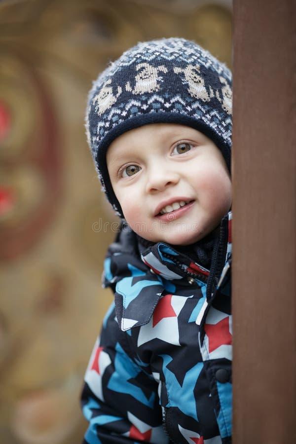 Χαριτωμένο μικρό παιδί που κοιτάζει αδιάκριτα γύρω από μια πόρτα στοκ εικόνα
