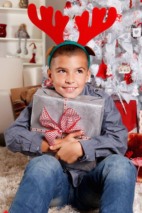 Χαριτωμένο μικρό παιδί που κρατά ένα δώρο Χριστουγέννων στοκ εικόνα