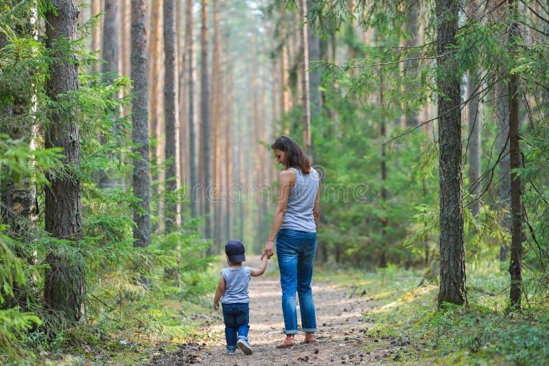 Χαριτωμένο μικρό παιδί που περπατά στο χέρι γονέων εκμετάλλευσης πάρκων Ευτυχής έννοια οικογενειών και τρόπου ζωής στοκ φωτογραφίες με δικαίωμα ελεύθερης χρήσης