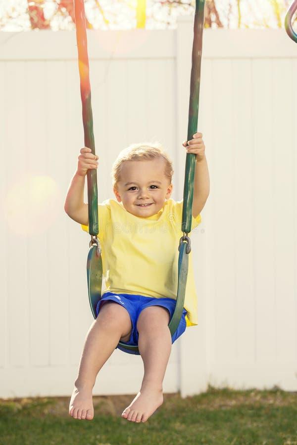 Χαριτωμένο μικρό παιδί που χαμογελά και που παίζει στην υπαίθρια ταλάντευση στοκ φωτογραφία