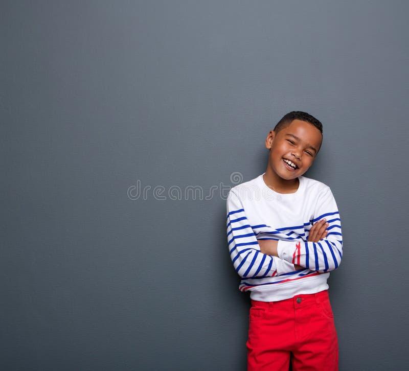 Χαριτωμένο μικρό παιδί που χαμογελά με τα όπλα που διασχίζονται στοκ εικόνες