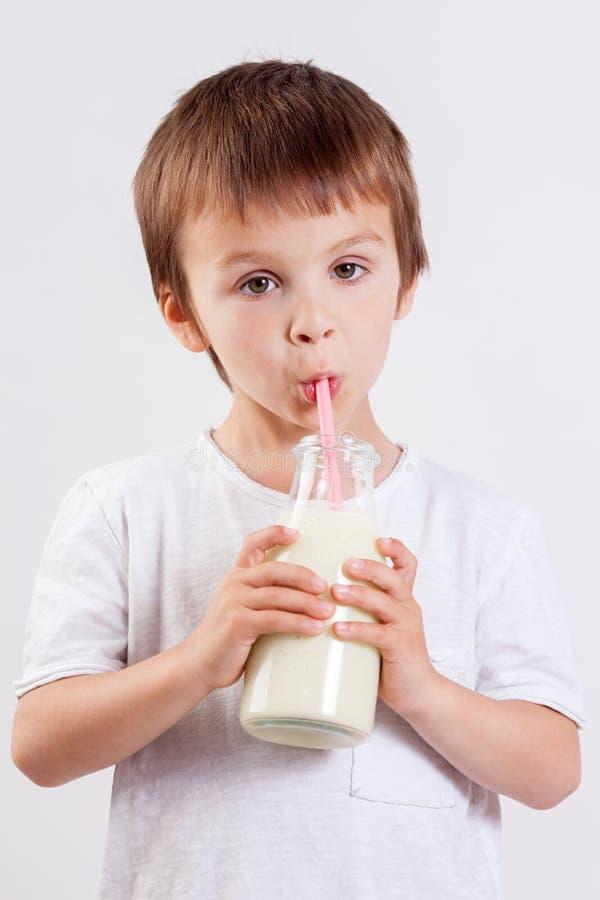 Χαριτωμένο μικρό παιδί, πόσιμο γάλα, που κρατά το ποτήρι του γάλακτος, mustaches στοκ εικόνα