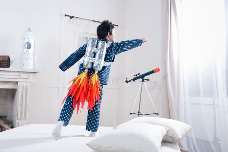 Χαριτωμένο μικρό παιδί στις πυτζάμες που παίζει τον αστροναύτη στο κρεβάτι στοκ εικόνες με δικαίωμα ελεύθερης χρήσης