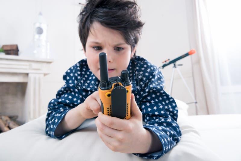 Χαριτωμένο μικρό παιδί στις πυτζάμες που χρησιμοποιούν walkie-talkie στοκ φωτογραφίες