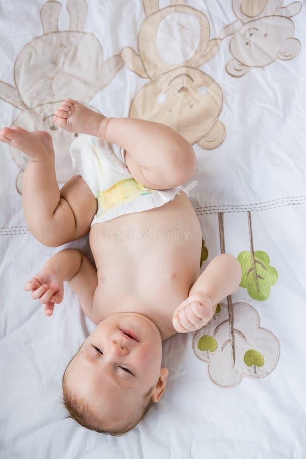 Χαριτωμένο μωρό που βρίσκεται στο κρεβάτι στην κρεβατοκάμαρα στοκ φωτογραφία