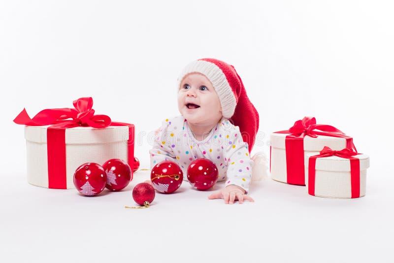 Χαριτωμένο μωρό που βρίσκεται στο στομάχι του σε ένα νέο έτος ` s ΚΑΠ μεταξύ Christm στοκ εικόνα