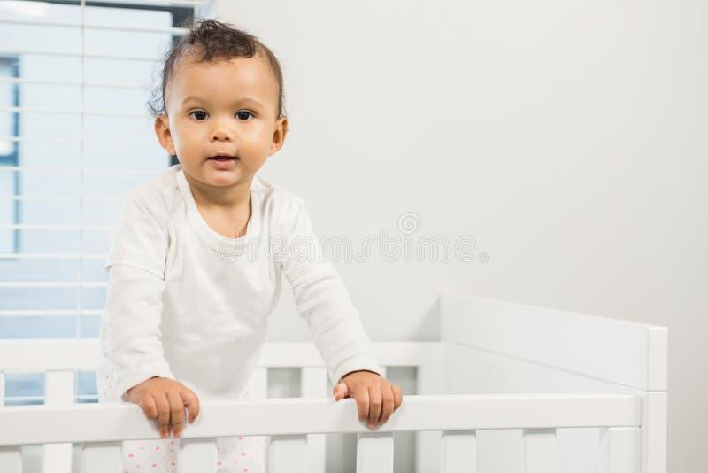 Χαριτωμένο μωρό που στέκεται στο παχνί στοκ εικόνα με δικαίωμα ελεύθερης χρήσης