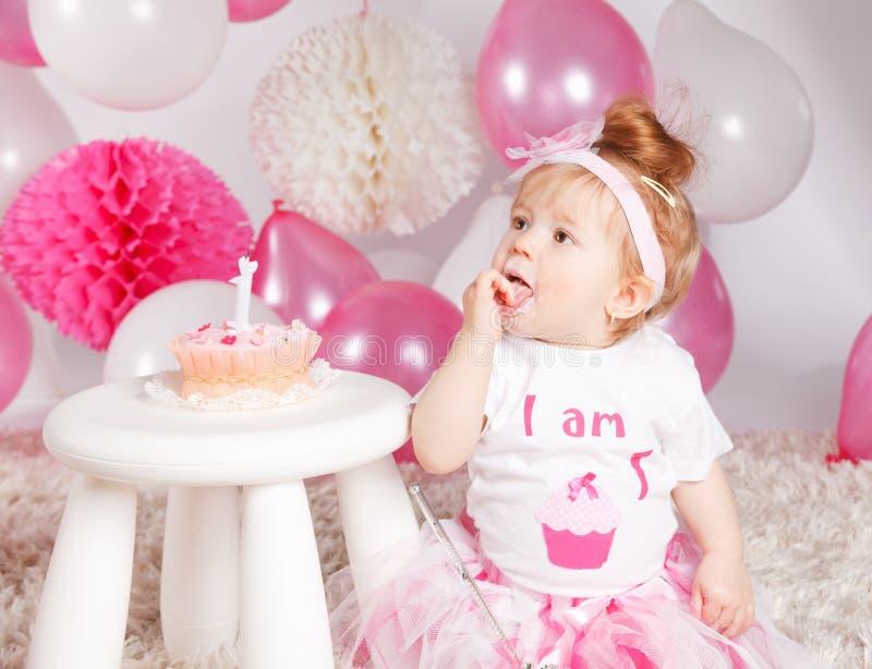 Χαριτωμένο μωρό που τρώει το κέικ γενεθλίων στοκ εικόνες