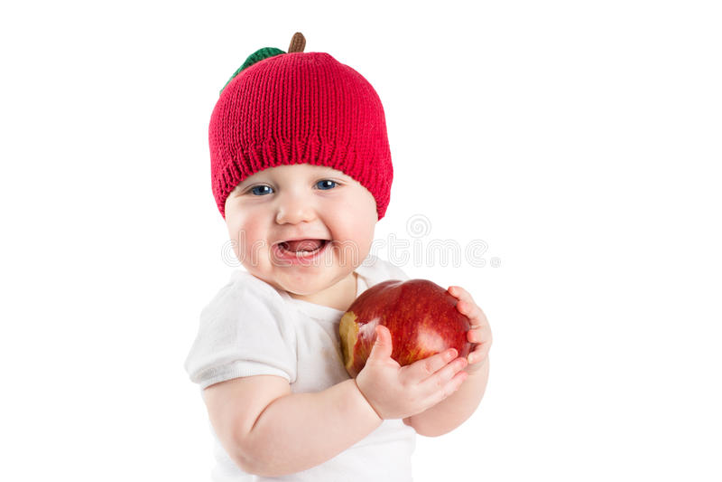 Χαριτωμένο μωρό σε ένα πλεκτό δάγκωμα καπέλων μήλων σε ένα κόκκινο ώριμο μήλο, που απομονώνεται στο λευκό στοκ φωτογραφίες
