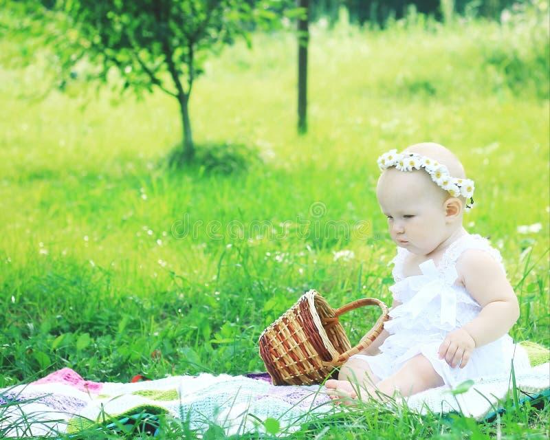 Χαριτωμένο μωρό σε ένα στεφάνι σε ένα πικ-νίκ μια θερινή ημέρα στοκ εικόνες