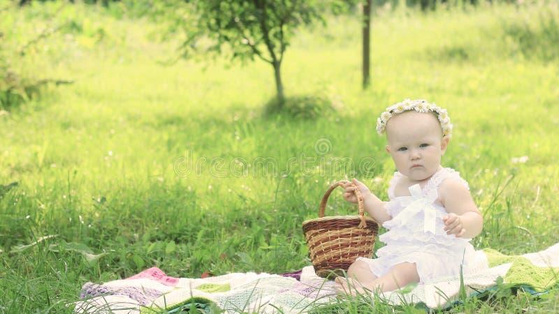 Χαριτωμένο μωρό σε ένα στεφάνι σε ένα πικ-νίκ μια θερινή ημέρα στοκ φωτογραφία