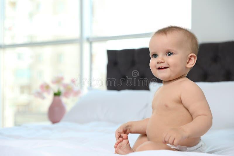 Χαριτωμένο μωρό στην πάνα στο κρεβάτι στο σπίτι στοκ φωτογραφίες με δικαίωμα ελεύθερης χρήσης
