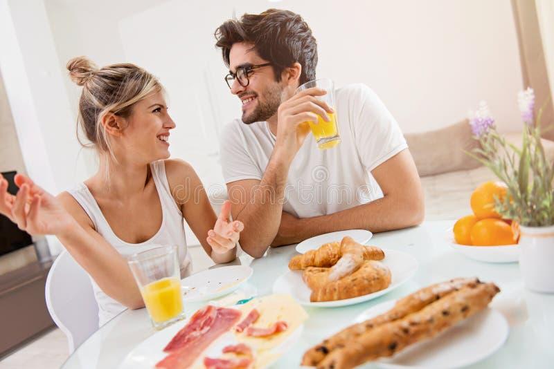 Χαριτωμένο νέο ζεύγος που απολαμβάνει το πρόγευμά τους από κοινού στοκ φωτογραφία