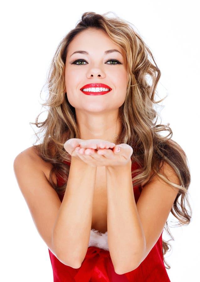 Χαριτωμένο νέο θηλυκό στο κόκκινο φόρεμα που φυσά ένα φιλί σε σας στοκ εικόνες