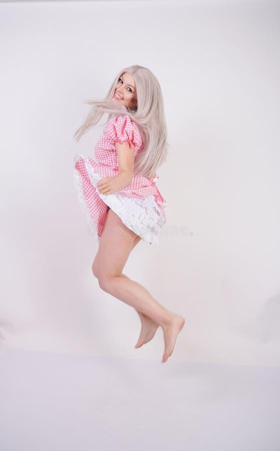 Χαριτωμένο νέο καυκάσιο κορίτσι εφήβων στο ρόδινο βαυαρικό φόρεμα καρό με την τοποθέτηση ποδιών στις άσπρες σταθερές βάσεις στούν στοκ φωτογραφία
