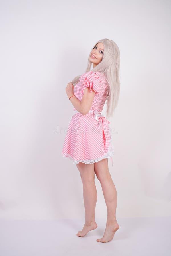 Χαριτωμένο νέο καυκάσιο κορίτσι εφήβων στο ρόδινο βαυαρικό φόρεμα καρό με την τοποθέτηση ποδιών στις άσπρες σταθερές βάσεις στούν στοκ φωτογραφίες