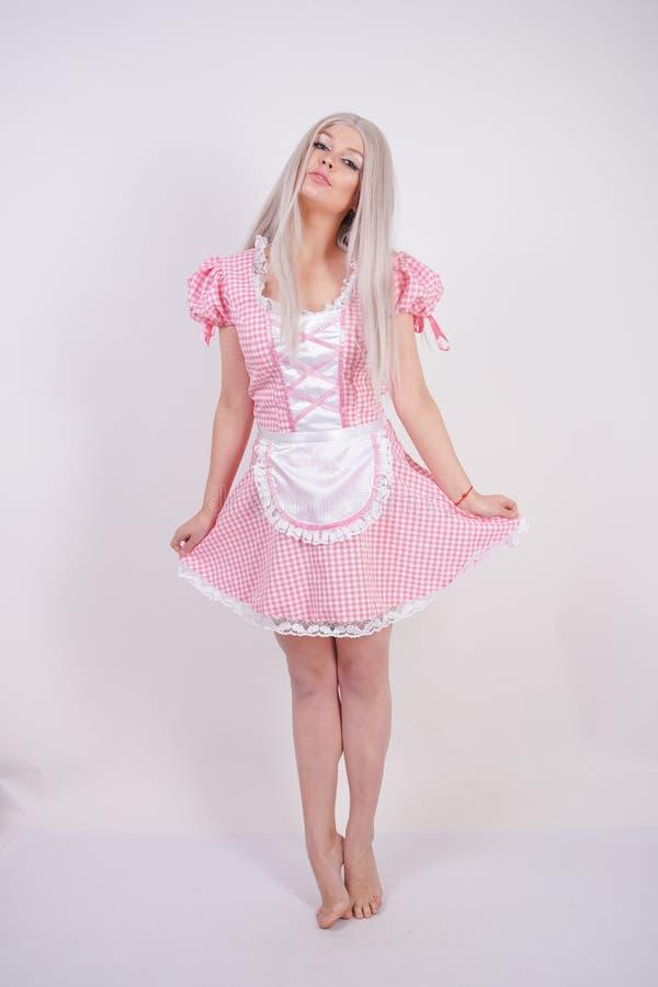 Χαριτωμένο νέο καυκάσιο κορίτσι εφήβων στο ρόδινο βαυαρικό φόρεμα καρό με την τοποθέτηση ποδιών στις άσπρες σταθερές βάσεις στούν στοκ εικόνες