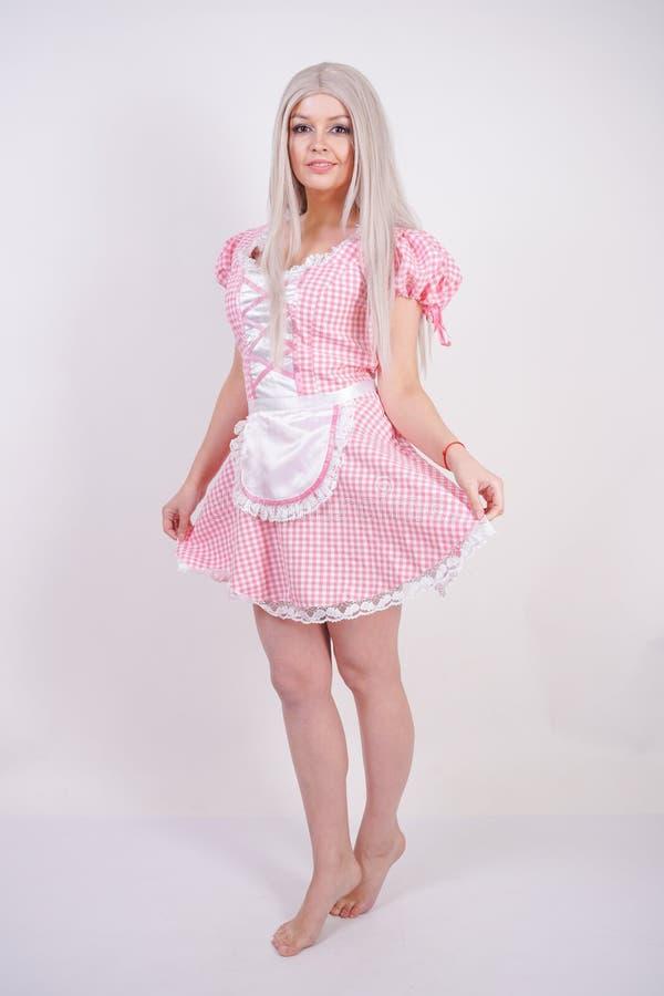 Χαριτωμένο νέο καυκάσιο κορίτσι εφήβων στο ρόδινο βαυαρικό φόρεμα καρό με την τοποθέτηση ποδιών στις άσπρες σταθερές βάσεις στούν στοκ εικόνα με δικαίωμα ελεύθερης χρήσης