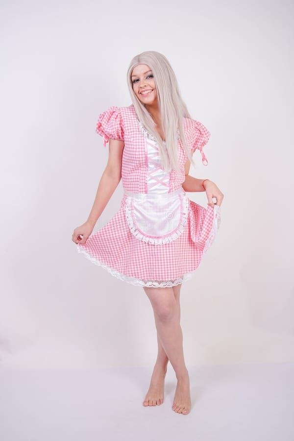 Χαριτωμένο νέο καυκάσιο κορίτσι εφήβων στο ρόδινο βαυαρικό φόρεμα καρό με την τοποθέτηση ποδιών στις άσπρες σταθερές βάσεις στούν στοκ εικόνα