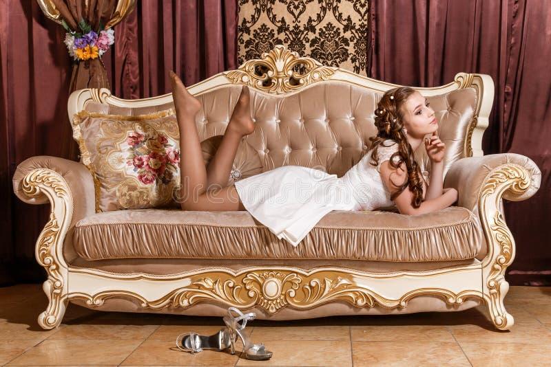 Χαριτωμένο νέο κορίτσι που βάζει σε έναν καναπέ στοκ εικόνα