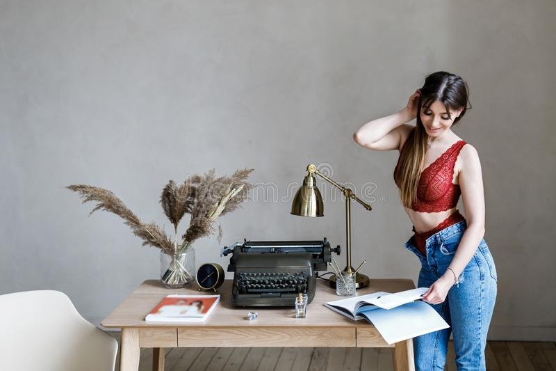 Χαριτωμένο νέο κορίτσι - brunette στο όμορφο εσώρουχο και τζιν που στέκονται στον υπολογιστή γραφείου στοκ εικόνες με δικαίωμα ελεύθερης χρήσης