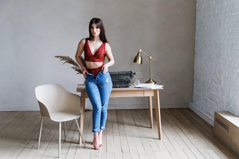 Χαριτωμένο νέο κορίτσι - brunette στο όμορφο εσώρουχο και τζιν που στέκονται στον υπολογιστή γραφείου στοκ φωτογραφίες