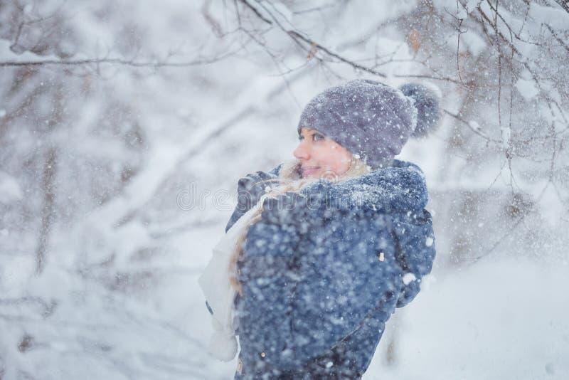 Χαριτωμένο νέο παιχνίδι πορτρέτου γυναικών με το χιόνι στο θερμό μάλλινο καπέλο και το παλτό στο χειμερινό πάρκο στοκ φωτογραφία με δικαίωμα ελεύθερης χρήσης