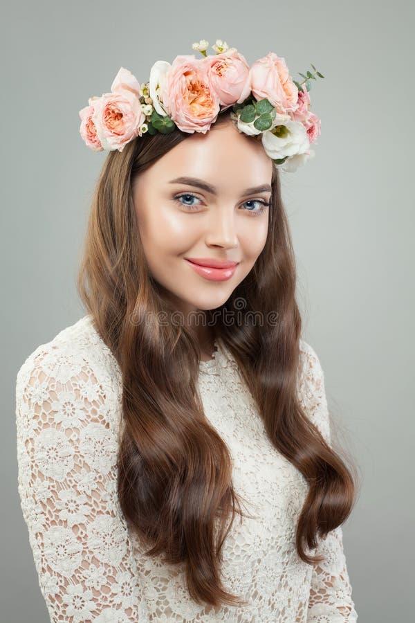 Χαριτωμένο νέο χαμόγελο γυναικών Το αρκετά πρότυπο κορίτσι με το σαφές δέρμα, το μακροχρόνια σγουρά hairstyle και τα λουλούδια στ στοκ φωτογραφία