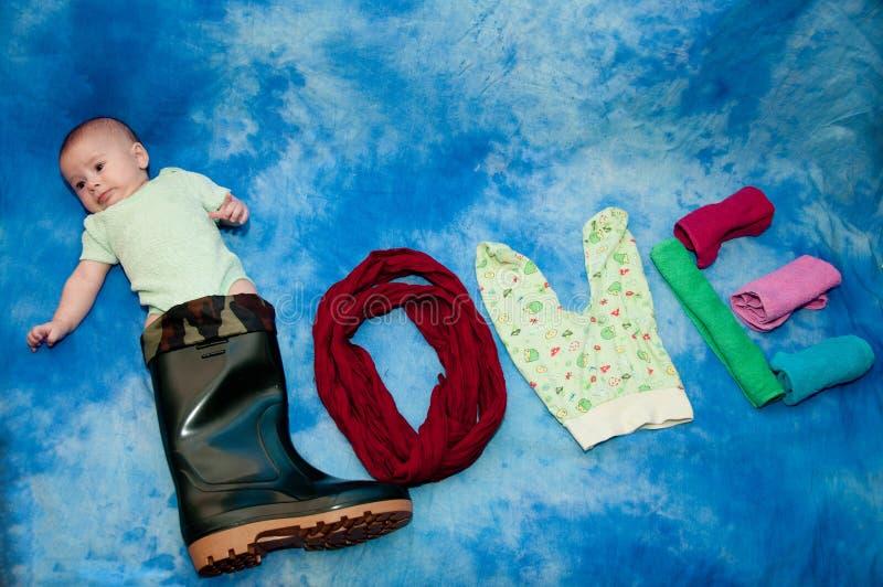 Χαριτωμένο νήπιο που βάζει στη μεγάλες μαύρες μπότα και τις πετσέτες, romper κοστούμι στο μπλε υπόβαθρο στοκ εικόνες