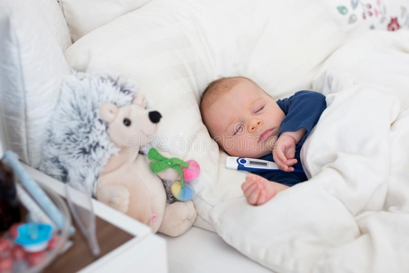 Χαριτωμένο νεογέννητο αγοράκι, που βρίσκεται στο κρεβάτι με το κρύο στοκ εικόνα με δικαίωμα ελεύθερης χρήσης