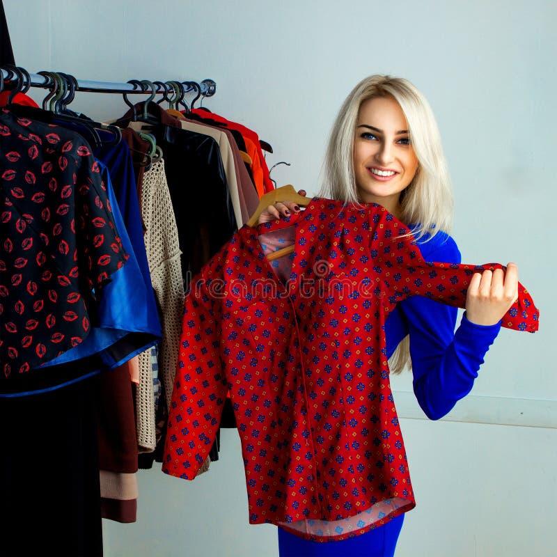 Χαριτωμένο ξανθό κορίτσι που χαμογελά και που επιλέγει το κόκκινο πουκάμισο στο stor ιματισμού στοκ φωτογραφία με δικαίωμα ελεύθερης χρήσης
