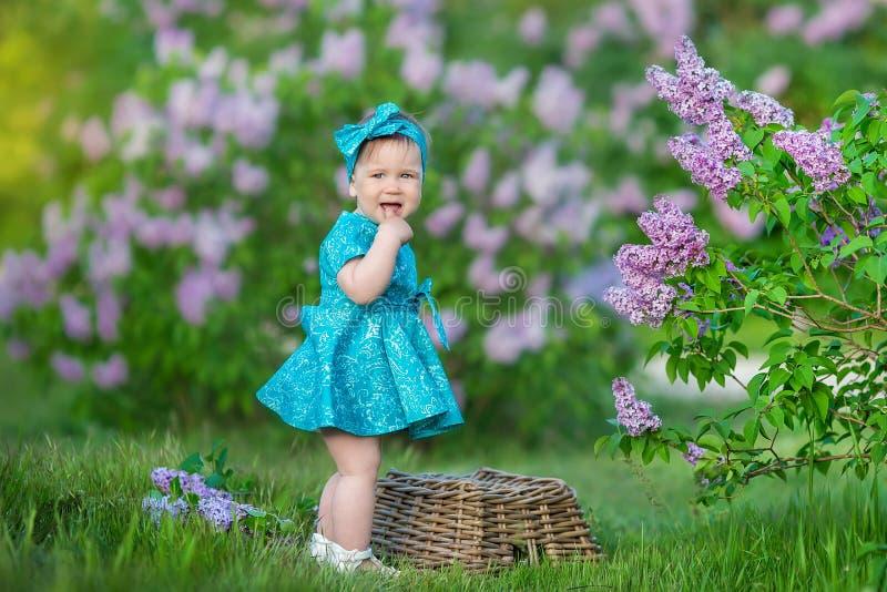 Χαριτωμένο ξανθό κοριτσάκι που απολαμβάνει το χρόνο σε μια τρομερή θέση μεταξύ του ιώδους θάμνου συρίγγων Νέα κυρία με το σύνολο  στοκ εικόνες