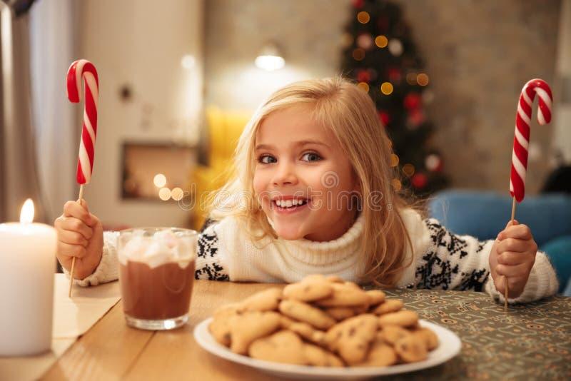 Χαριτωμένο ξανθό παιδί με δύο καλάμους καραμελών που κάθεται στον εορταστικό πίνακα στοκ εικόνες