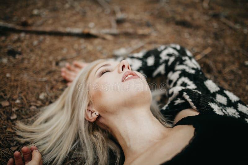 Χαριτωμένο ξανθό womann που ξαπλώνει στο δασικό έδαφος στοκ φωτογραφίες
