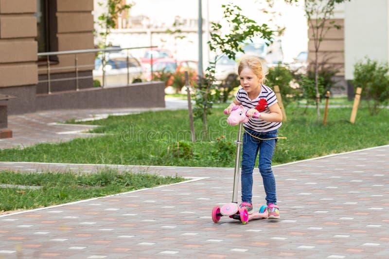 Χαριτωμένο οδηγώντας μηχανικό δίκυκλο μικρών κοριτσιών στο πάρκο πόλεων τη φωτεινή θερινή ημέρα Ξανθό μικρό παιδί που έχει τη δια στοκ εικόνες