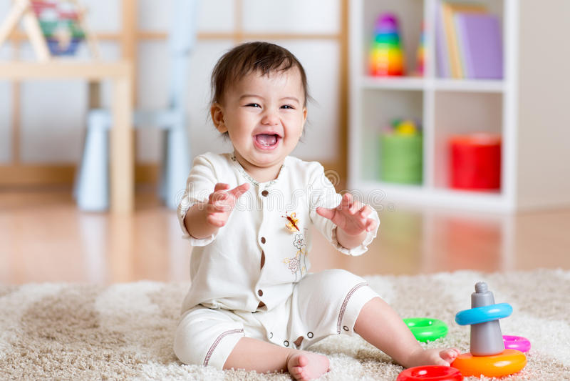 Χαριτωμένο παίζοντας σπίτι μωρών νέων κοριτσιών με τα ζωηρόχρωμα παιχνίδια στοκ εικόνα με δικαίωμα ελεύθερης χρήσης
