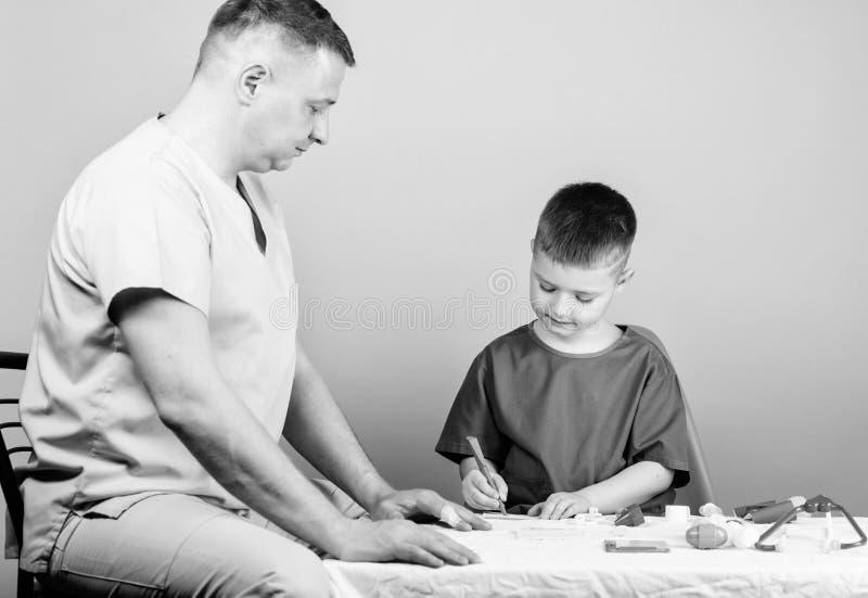 Χαριτωμένο παιδί αγοριών και ο γιατρός πατέρων του r Πρώτες βοήθειες Ιατρική βοήθεια Τραύμα και injurie r στοκ φωτογραφίες με δικαίωμα ελεύθερης χρήσης