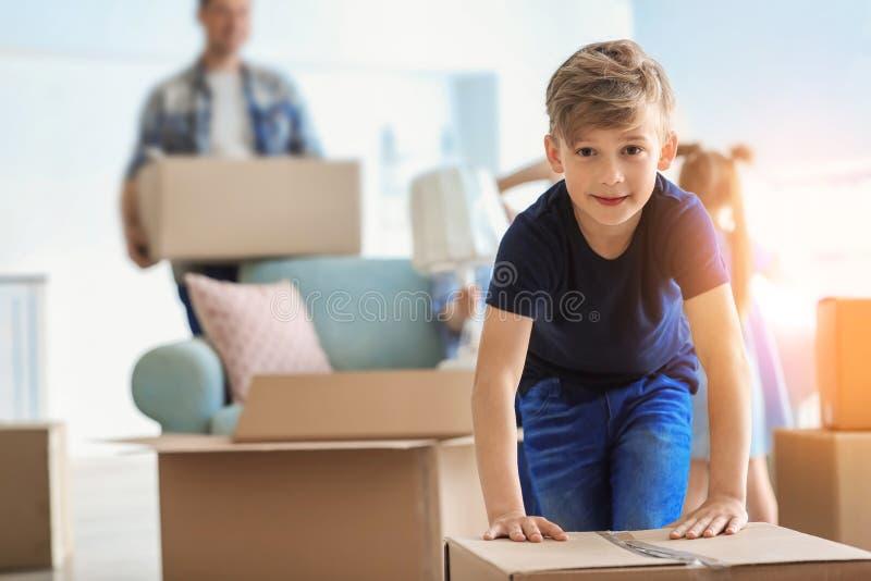 Χαριτωμένο παιδί με το κιβώτιο με τις περιουσίες οικογενειακής συσκευασίας του στο σπίτι Κίνηση στο καινούργιο σπίτι στοκ εικόνες