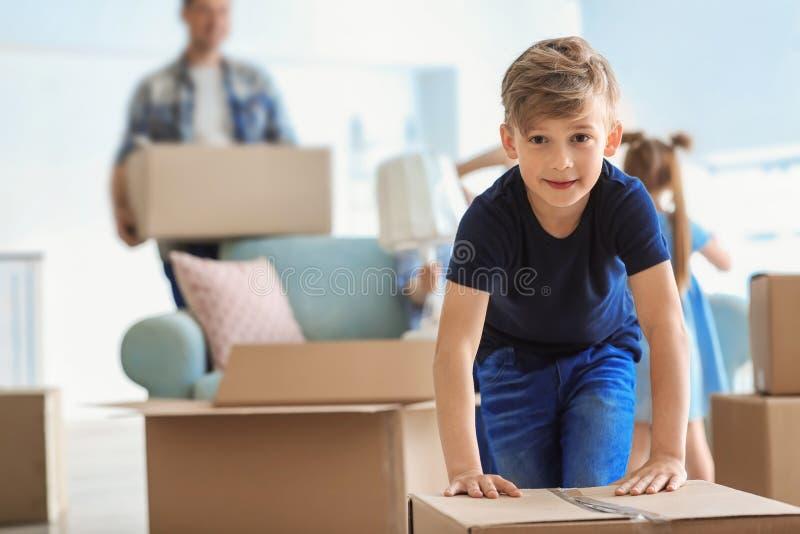 Χαριτωμένο παιδί με το κιβώτιο με τις περιουσίες οικογενειακής συσκευασίας του στο σπίτι Κίνηση στο καινούργιο σπίτι στοκ εικόνα με δικαίωμα ελεύθερης χρήσης