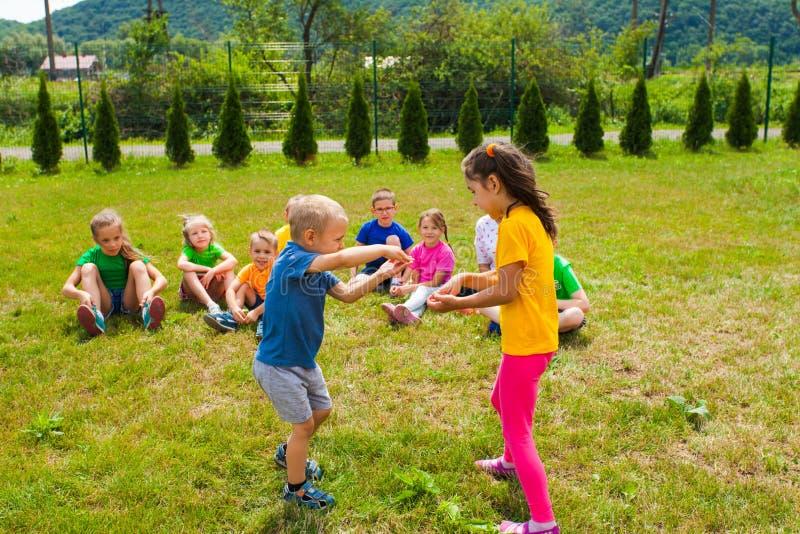 Χαριτωμένο παιχνίδι αγοριών και κοριτσιών μπροστά από τους φίλους τους στοκ φωτογραφία με δικαίωμα ελεύθερης χρήσης