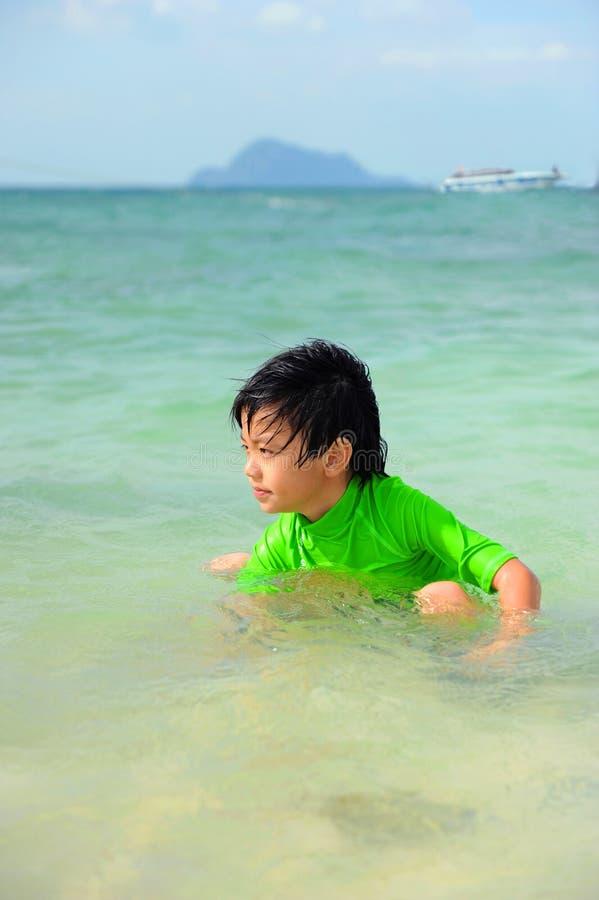 Χαριτωμένο παιχνίδι αγοριών στη θάλασσα στοκ φωτογραφία