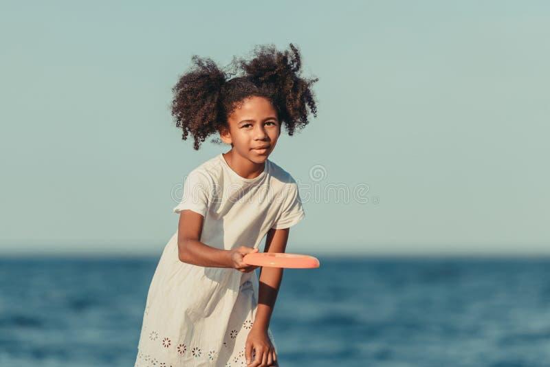 χαριτωμένο παιχνίδι κοριτσιών αφροαμερικάνων με τον πετώντας δίσκο και εξέταση τη κάμερα στοκ εικόνα