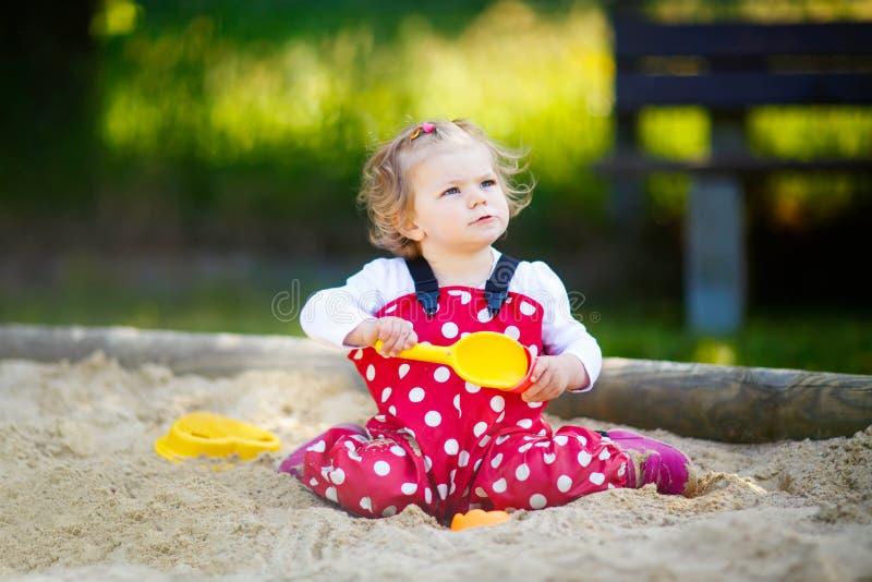 Χαριτωμένο παιχνίδι κοριτσιών μικρών παιδιών στην άμμο στην υπαίθρια παιδική χαρά Όμορφο μωρό στο κόκκινο παντελόνι γόμμας που έχ στοκ εικόνα