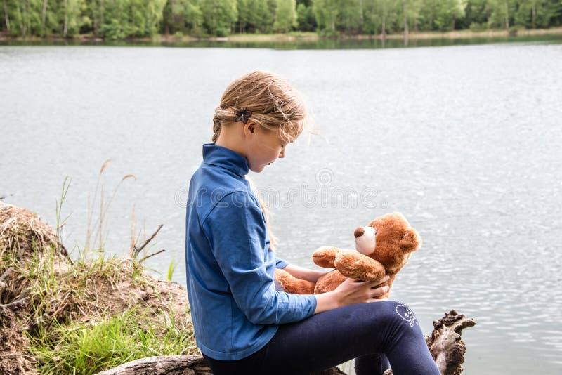 Χαριτωμένο παιχνίδι κοριτσιών Llittle με τη teddy αρκούδα στο καλοκαίρι υπαίθρια Έννοια φίλων στοκ εικόνα